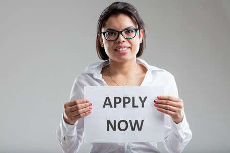 online form: woman holding an apply-now sign and smiling inviting you to fill in that (online) form