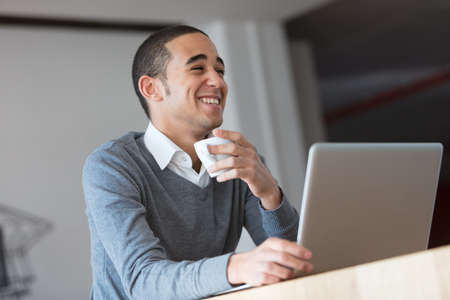openspace: laughter of a young businessman in a large house or an openspace, he drinks a coffee listening something funny as he uses his laptop