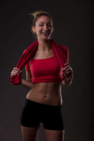 Happy athletic fit young woman at the gym posing with a towel around her shoulders laughing at the camera in a healthy lifestyle concept