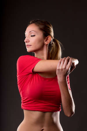 studio portrait of a woman making some arm stretching exercise to mantain a good flexibility of her biceps