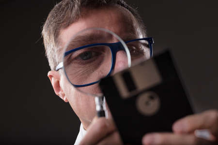 itc: concept of data recovery or forensics as an expert engineer carefully examining a floppy disk as an unknown antique and unknown technology to look for some lost data or malicious software