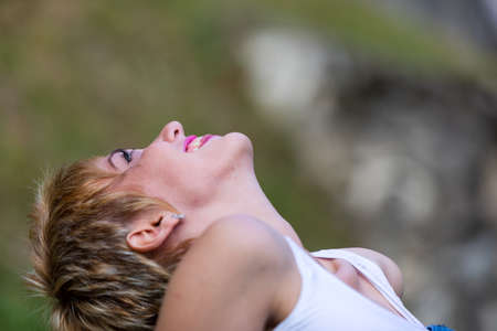 living moment: young blonde woman watching the sky lying on the green grass and smiling, living a relaxing moment in the nature