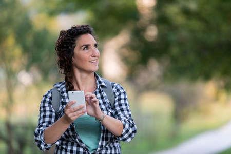 guia de turismo: mujer que viaja en la naturaleza usando su teléfono inteligente como un guía turístico