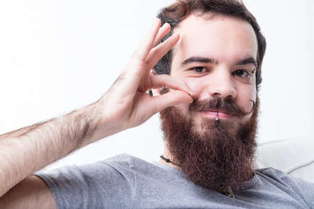 swanky: man with a thick beard proudly pinching his mustaches