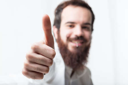 swanky: thumbs up (in focus) by a bearded man (out of focus) on the background