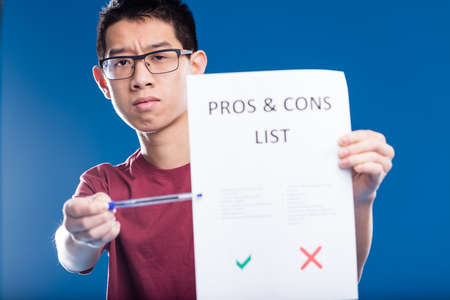 cons: pessimism concept: asian guy showing his negative point of view about a list of pros and cons