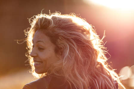 thru: woman on the sun is a young motorbiker with her long hair and the sun through them Stock Photo
