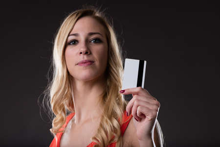 woman holding a powerful weapon: a credit card. is it hers or yours? lets find out Stock Photo