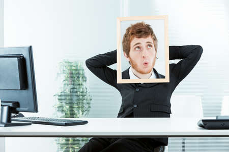 unresponsive: office worker with his arms relaxed and a picture frame with a photo of another face with a indifferent expression