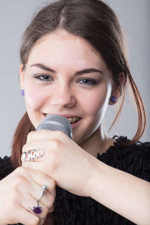 young smiling woman with braces on her teeth speaking or singing with a microphone