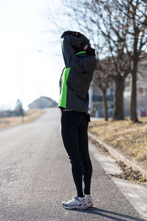 tiring: workout of a woman doing some stretching exercises as a warm-up before her daily training in the streets, she is ready to run