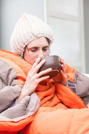 emphasized: funny exaggeration concept of an ill woman that has the flu as she drinks a hot chicken broth Stock Photo