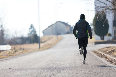 tiring: rear view of a woman running in the streets of a little town during winter or autumn
