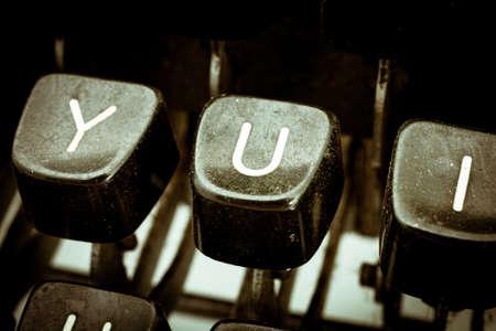 vowel: U letter closeup between other letters on an original vintage typewriters keyboard
