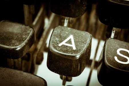 A letter closeup between other letters on an original vintage typewriters keyboard