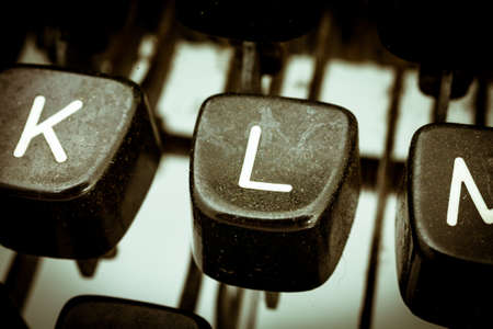 L letter closeup between other letters on an original vintage typewriters keyboard