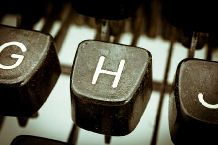 H letter closeup between other letters on an original vintage typewriters keyboard