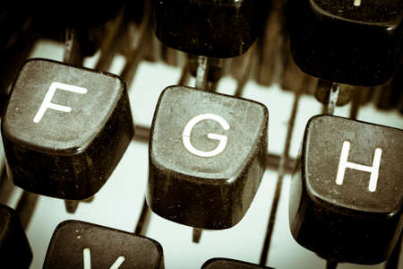 G letter closeup between other letters on an original vintage typewriters keyboard