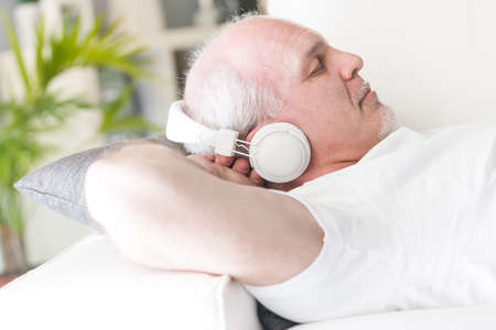 mature man with his hands behind the head sleeping or relaxing while listening to music on the headphones liying on a couch in his living room