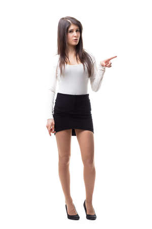 isolated on white, long haired woman with a short skirt and white sweaterand long legs on high heels pointing out her finger to some product or COPYSPACE Stock Photo