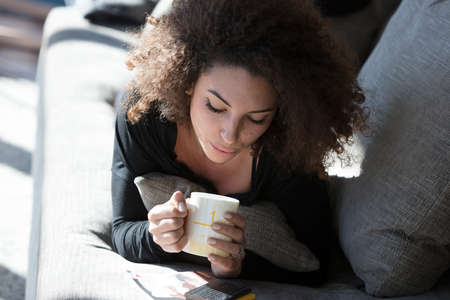 Lonely young woman enjoying a mug of coffee as she relaxes on the sofa in te summer sun looking down with downcast eyes