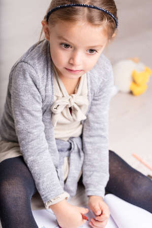 Pretty pensive little girl sitting on her bed with a sheet of paper and pencil staring down with big eyes and a thoughtful expression