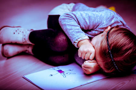 Upset little girl curled up on the bed next to her drawing rubbing her eyes with her fists as though crying, side vignette