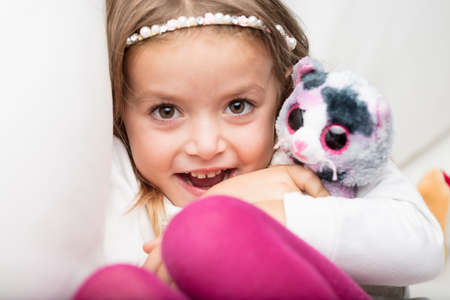 Cute laughing little girl with her favorite fluffy toy clasped tightly in her arms smiling at the camera as she cuddles down on a bed