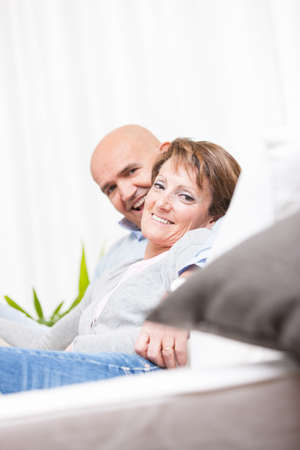 Relaxed attractive middle-aged woman turning to smile at the lens as she lies on a sofa snuggling against her husband