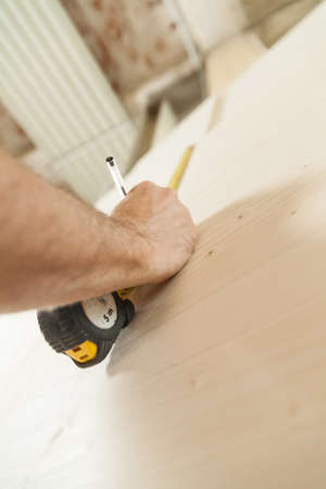 hands of a woodworker measuring with a tape and wiriting down on the wooden board with a pencil; concept of carpenter craftsman in his workshop Stock Photo