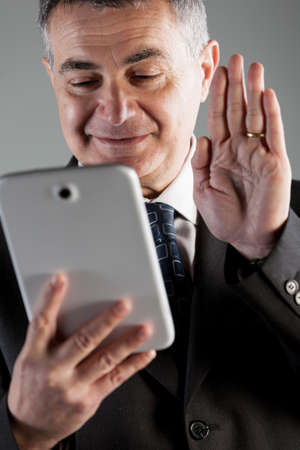 Businessman video conferencing waving at his tablet with a smile in a close up view with focus to his face and raised hand