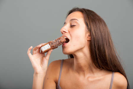 Sensual young woman biting into a chocolate covered ice cream bar with her eyes closed in bliss and anticipation, over a grey background