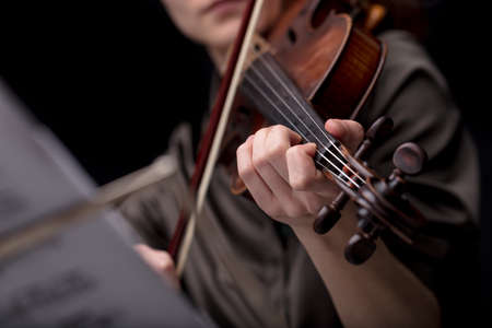 musical score: closeup of an unrecognizable musical players hand holding a violin while playing it. Portrait on a black room with music score blurred in foreground