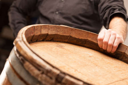 Man standing with his hand on a wooden oak barrel or cask in a winery, distillery or brewery for maturing the alcohol in a conceptual close up image