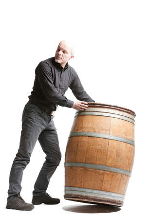 Middle-aged man tilting a large wooden cask or barrel as he looks back over his shoulder isolated on white