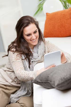 Smiling young woman browsing on a tablet computer as she sits on the floor leaning against a sofa in the living room