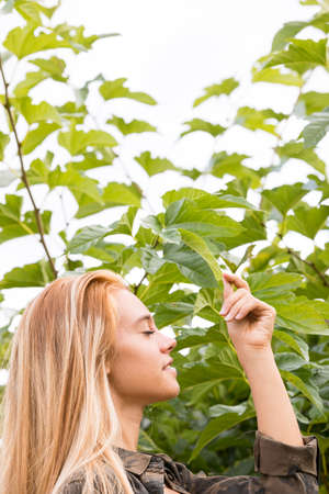 blond beautiful girl loving nature outdoors as she touches a green leaf respecting its spirit Stock Photo