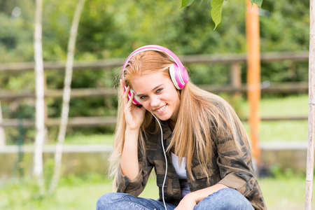 jugando videojuegos: pretty girl with pink headphones listening to her favourite music on her favorite mobile device, maybe a mobile phone Foto de archivo