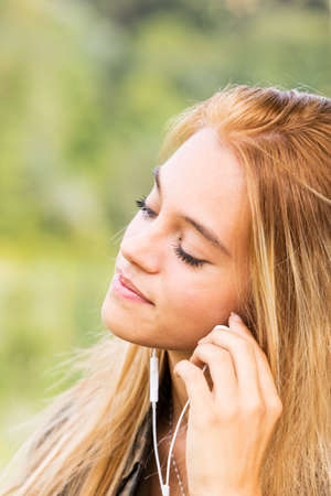 maybe: outdoors portrait of a beautiful blond girl using white earphones to listen to her favorite music, maybe on her mobile phone or mp3 player