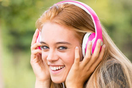 pretty girl with pink headphones listening to her favourite music on her favorite mobile device, maybe a mobile phone Stock Photo