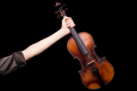 pegheads: right arm of a female violin player rising out and holding an handcrafted violin on a black background with lots of copyspace around