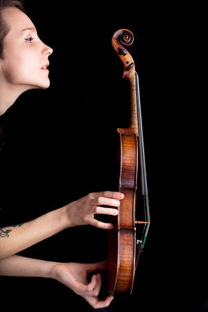 pegheads: woman profile with violin on a black background
