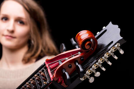 pegheads: woman playing an ancient medieval musical instrument, modern reconstruction of an antique nyckelharpa, often used in folk or baroque musical concerts or dances Stock Photo