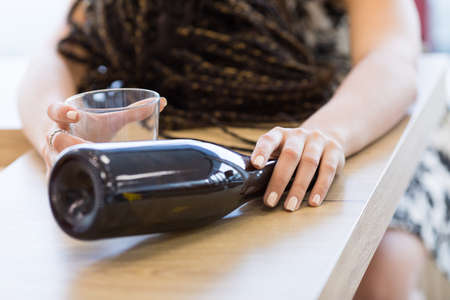 inebriated: Close-up of incognito woman lying on table face down holding a bottle and a glass in her hands Stock Photo