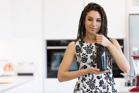 unlabelled: Portrait of young brunette with braids hairstyle standing in the kitchen in flourish pattern dress, holding a bottle, looking at camera and smiling. Copy space