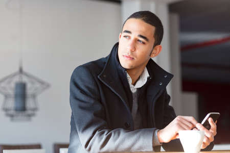 Young man in black coat on sunny day sitting indoors with a cup of coffee, looking away thoughtfully while holding a cell phone