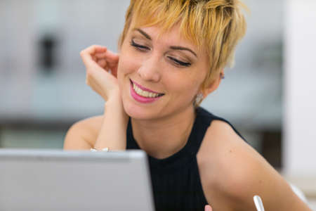 Smiling young blond businesswoman looking at laptop computer screen Stock Photo