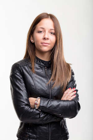 Confident young woman in a black leather jacket standing with her arms folded looking at the camera with a quiet smile, upper body on white