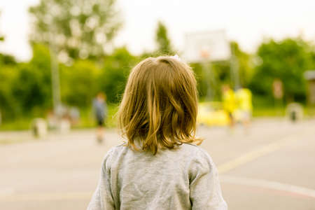little girl watching boys and girls as they play in the public basketball court