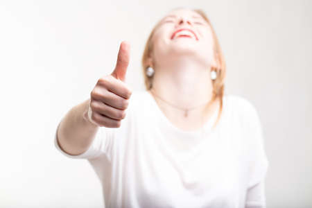 Elated excited woman giving a thumbs up gesture of success, victory and agreement as she throws back her head laughing over a white background